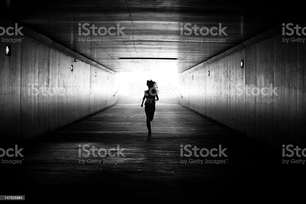 Black amd white image of girl running towards the light stock photo