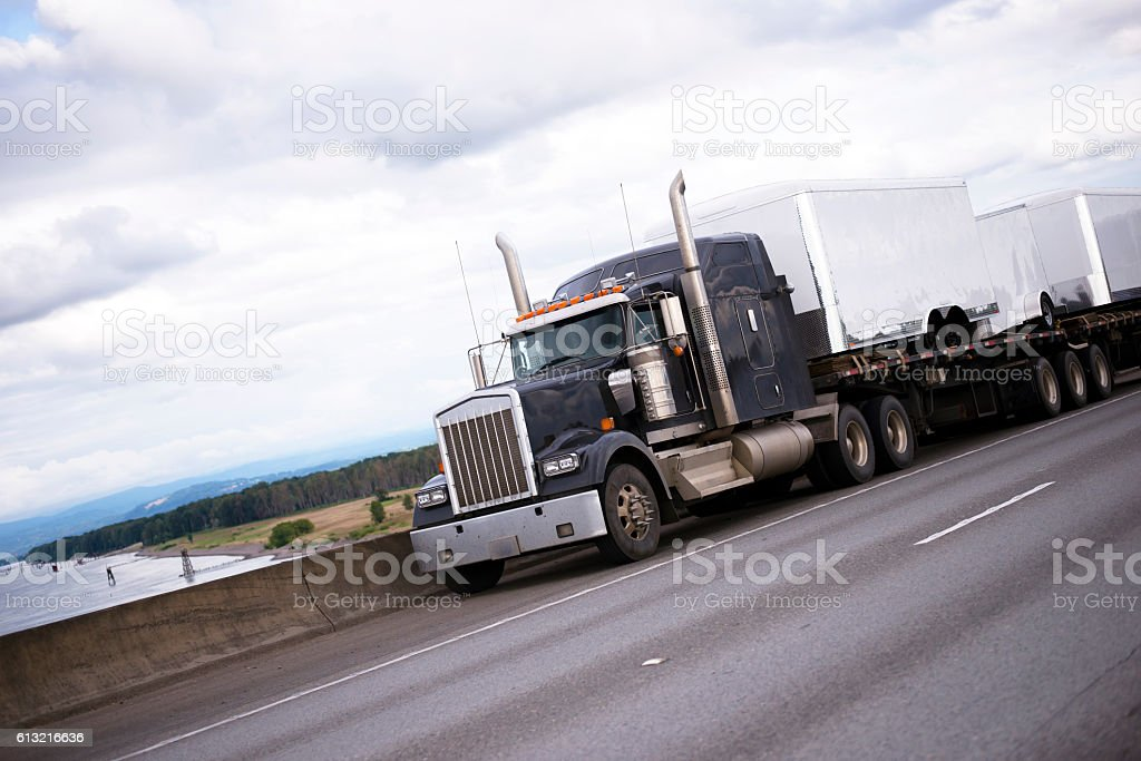 Black american big rig semi truck on interstate highway stock photo