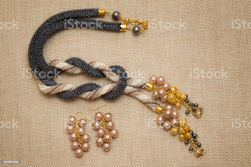 Black and beige crocheted necklace with golden pendants stock photo