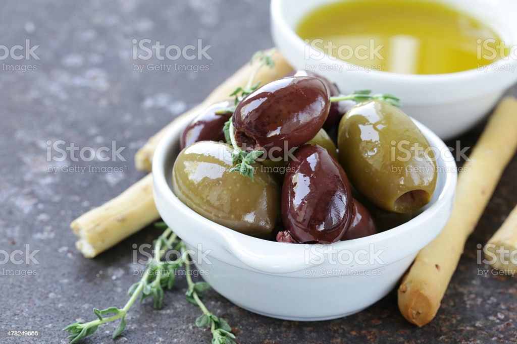 black and green olives in oil with herbs stock photo