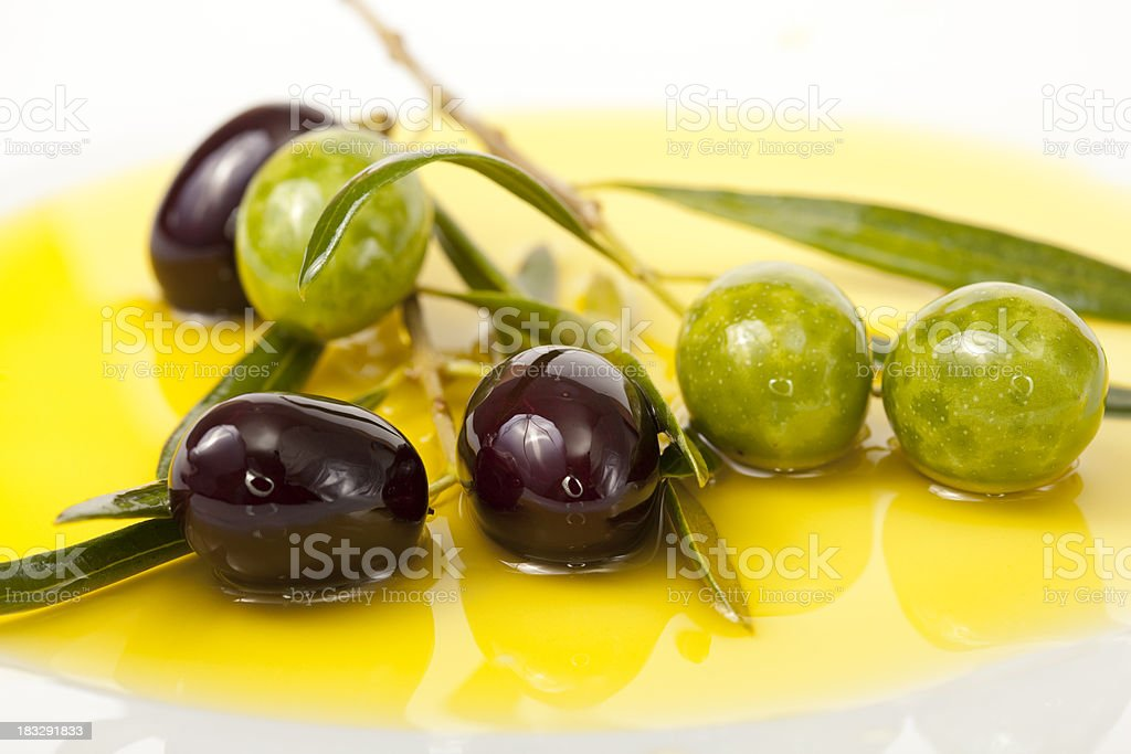 Black and Green Olives in olive oil background stock photo