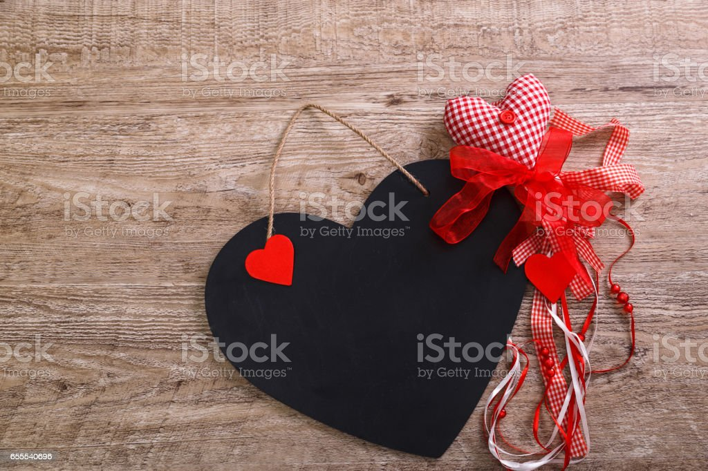 Black and red hearts on wooden background. stock photo