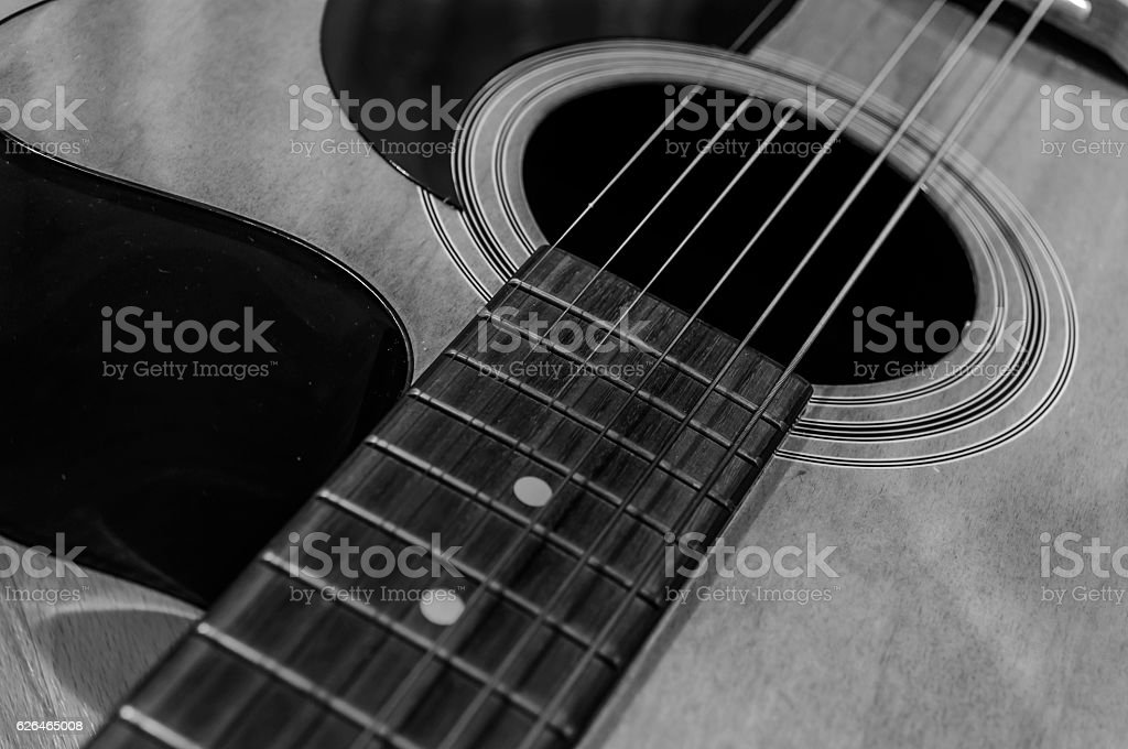 Black and white acoustic guitar with sound hole and pickguard stock photo