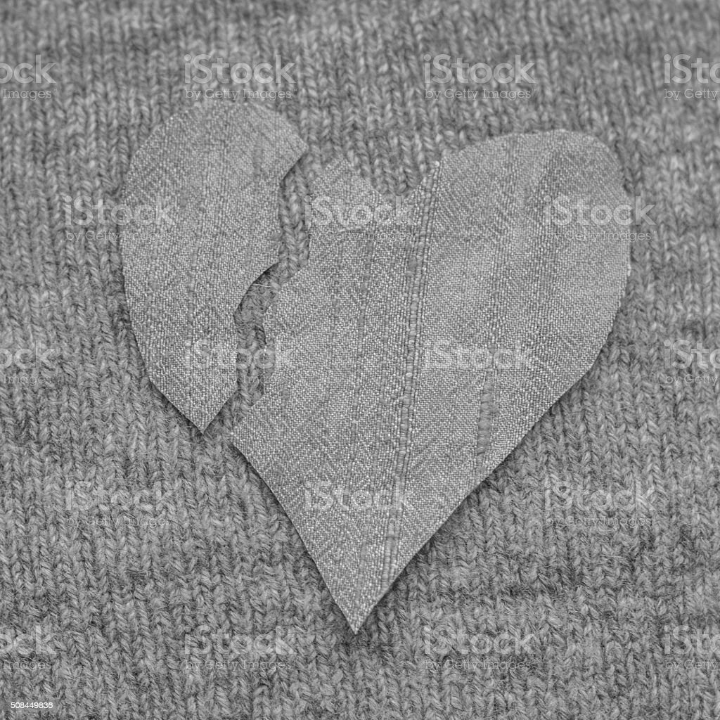 Black and white broken heart in silk on knitted background stock photo