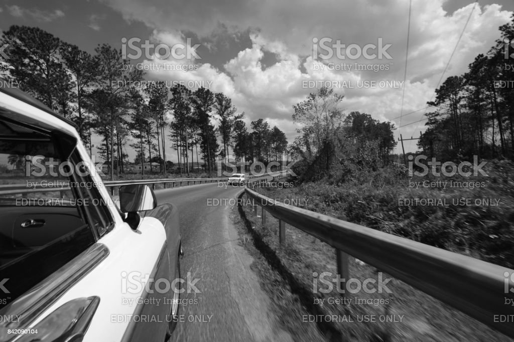 Black and white classic car following another car on a winding road in Cuba stock photo