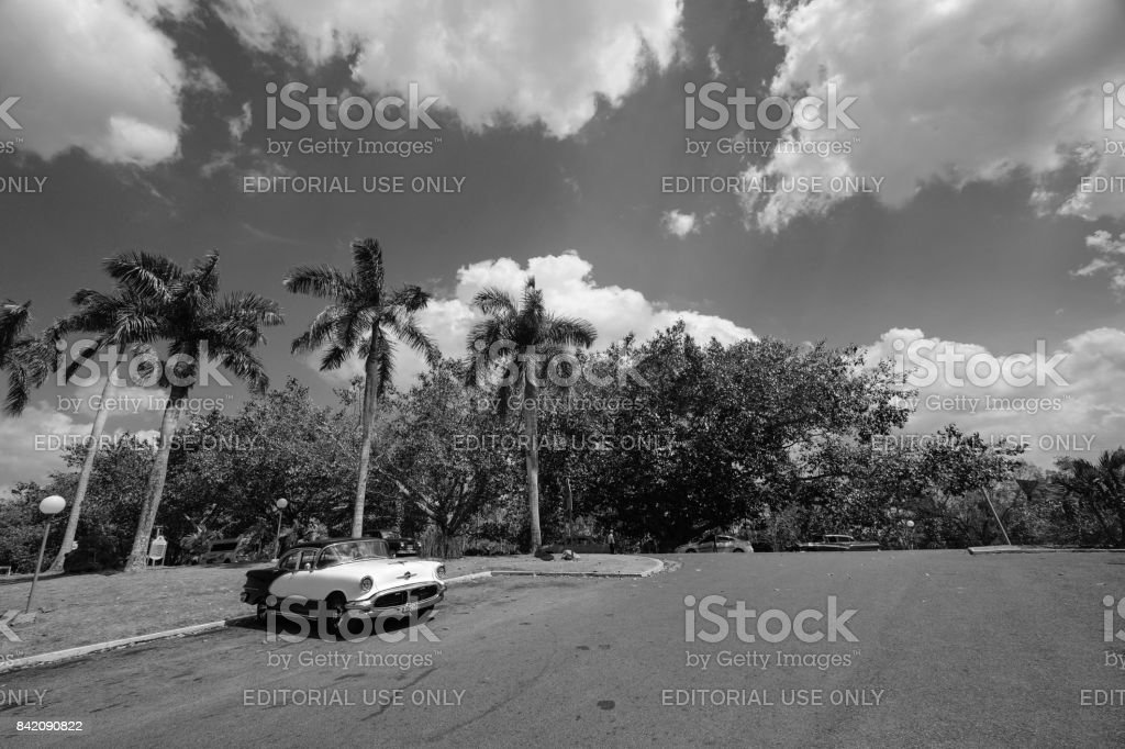 Black and white classic car in empty parking lot with palm trees in Cuba stock photo