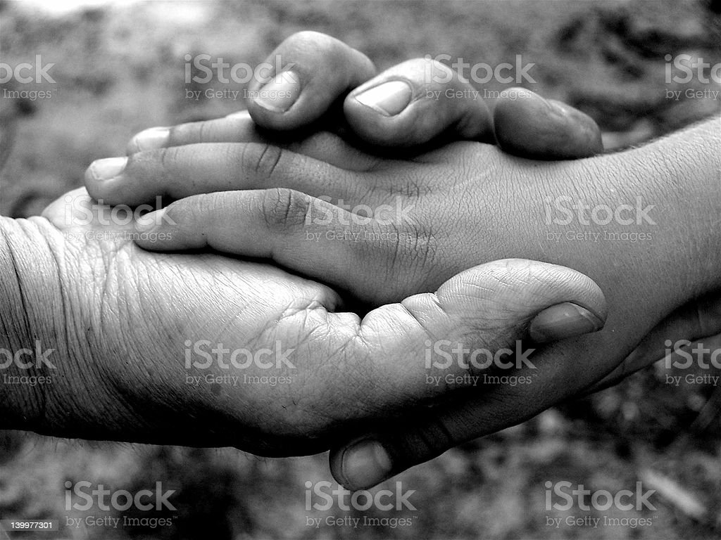 Black and white close-up photo of joined hands stock photo