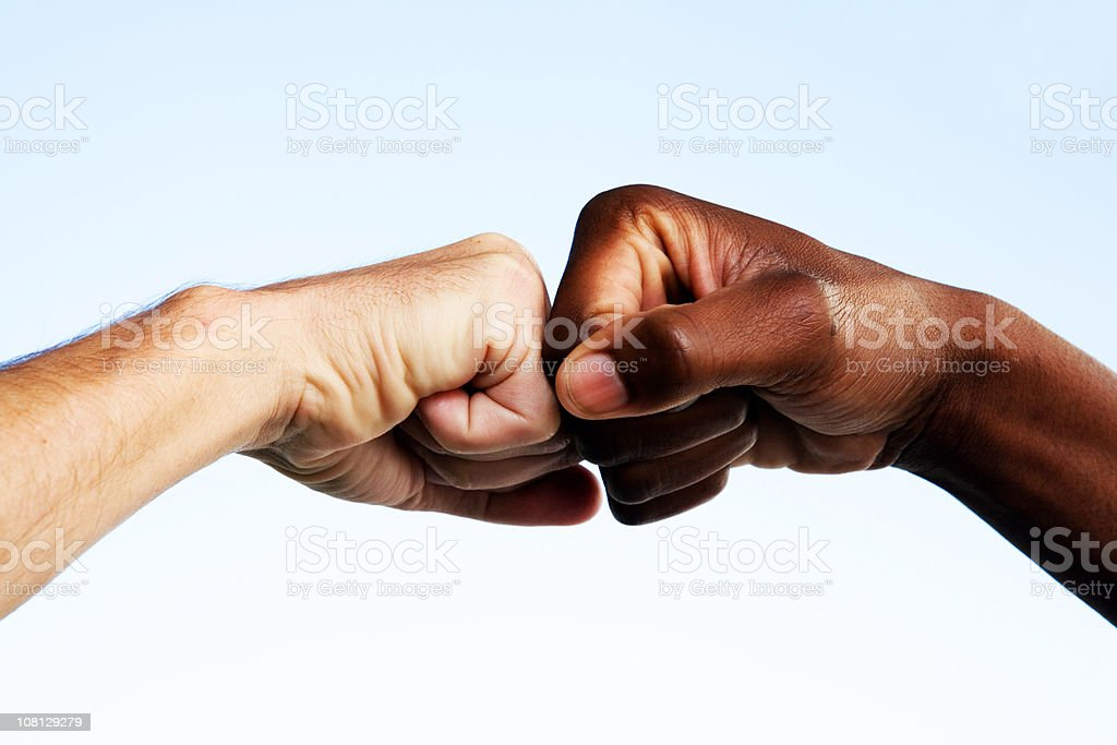 Black and white fists touching stock photo