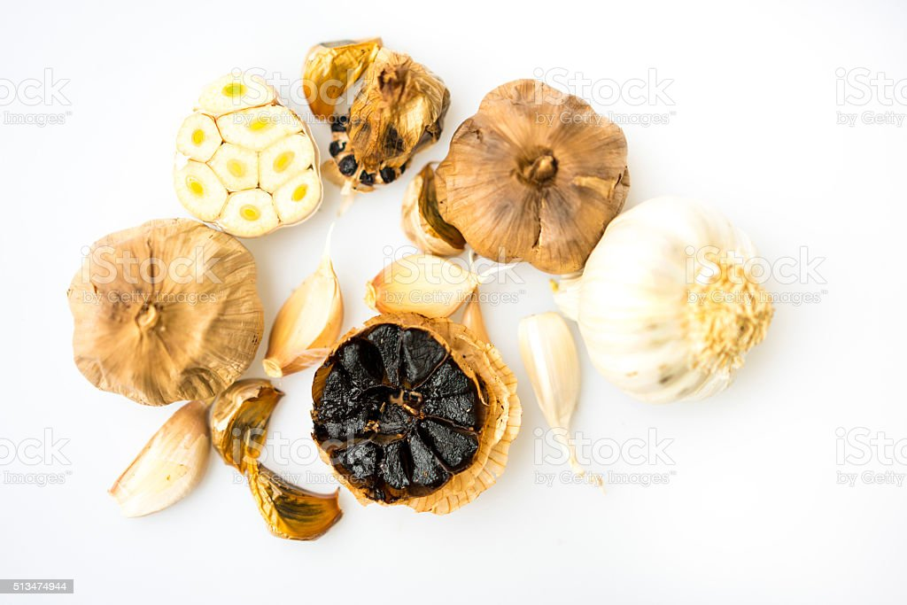 Black and white garlic isolated on white background stock photo