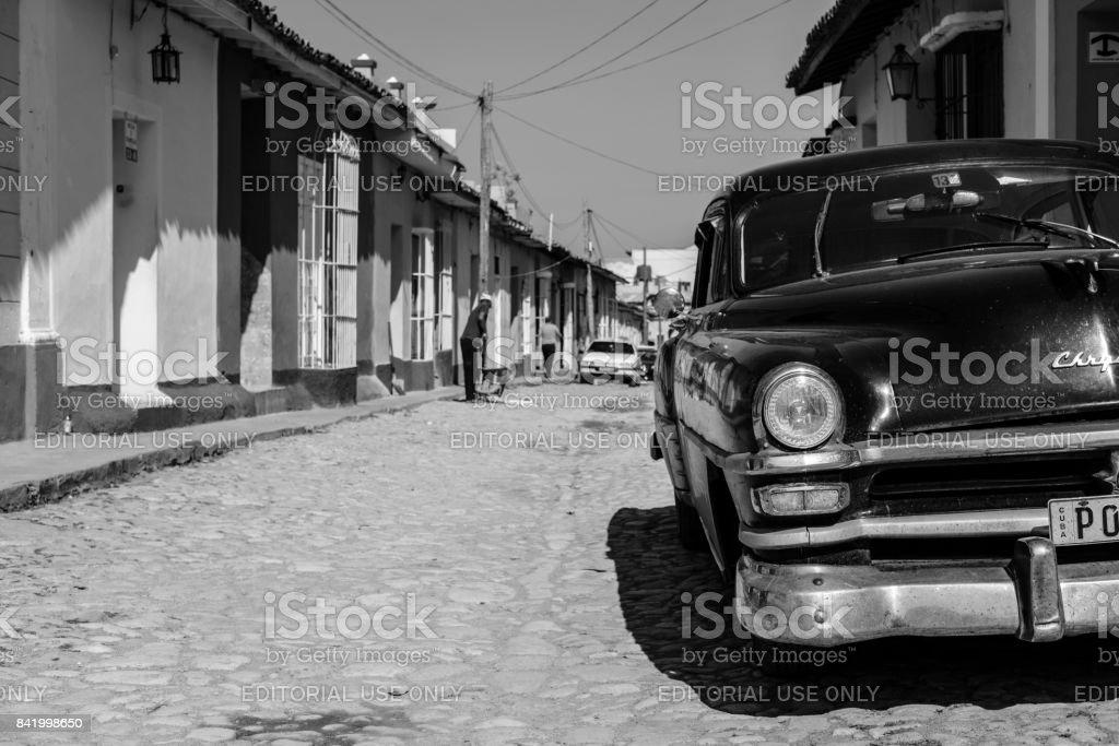 Black and white half-view of classic car on empty cobblestone street stock photo