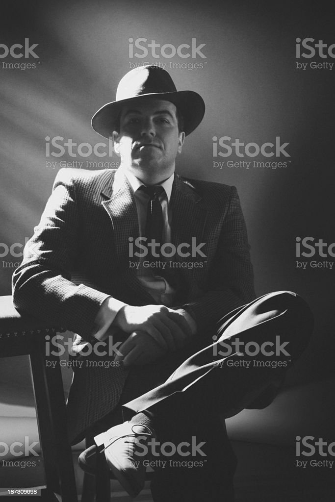 Black and white image of a 1940s style gangster sitting stock photo