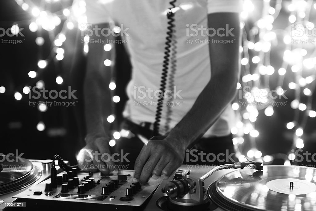 Black and white image of a DJ's hands mixing vinyl records stock photo