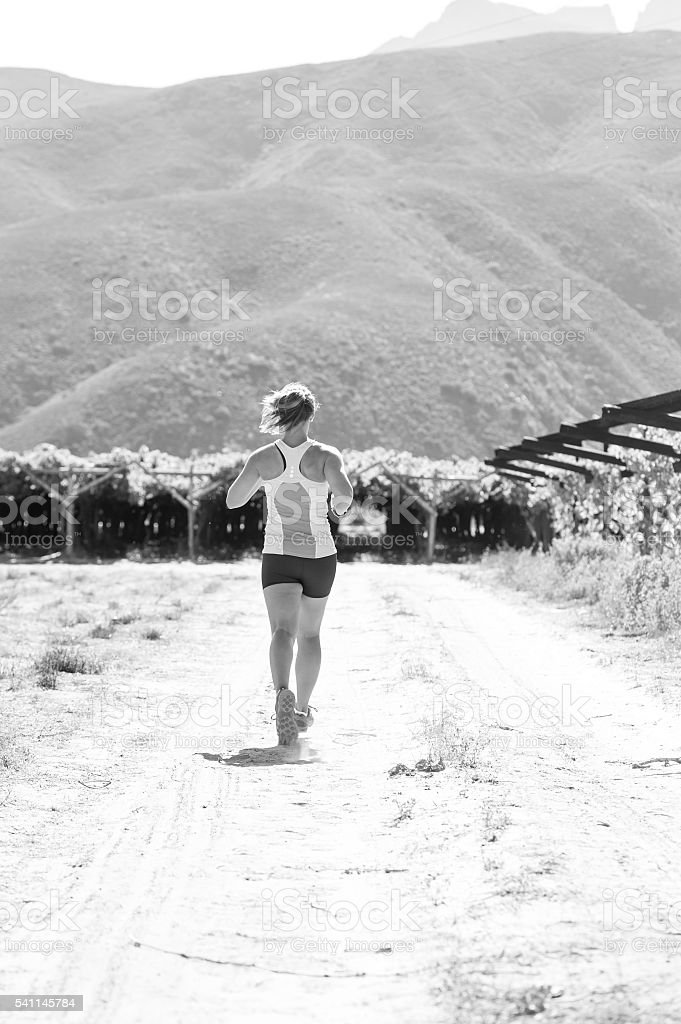 Black and white image of a female trail runner stock photo