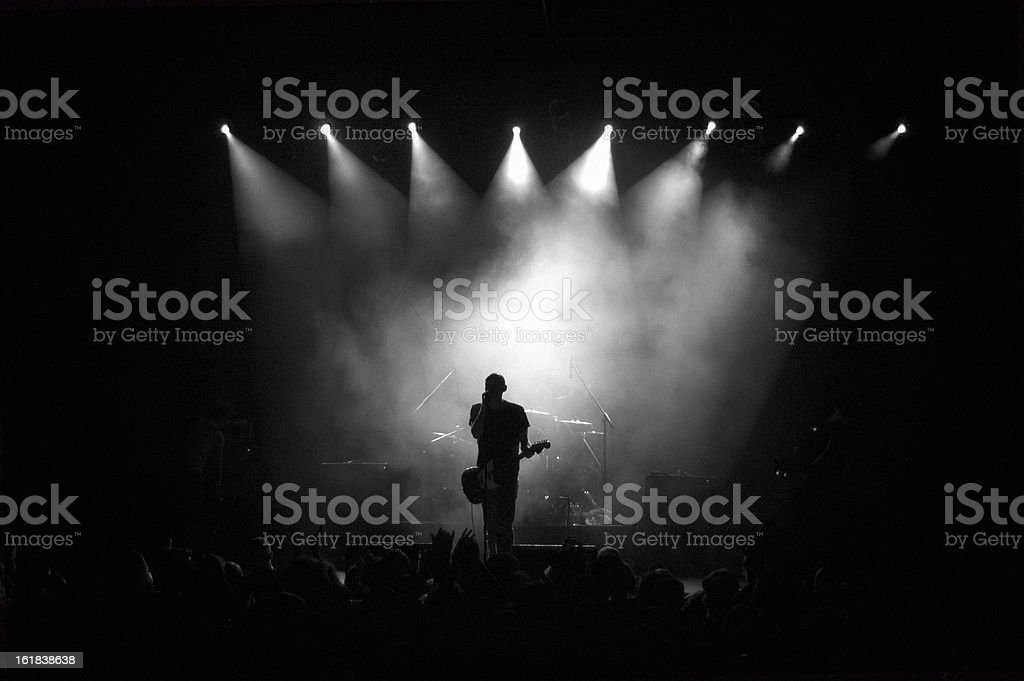 Black and white image of a guitarist on stage in fog  royalty-free stock photo