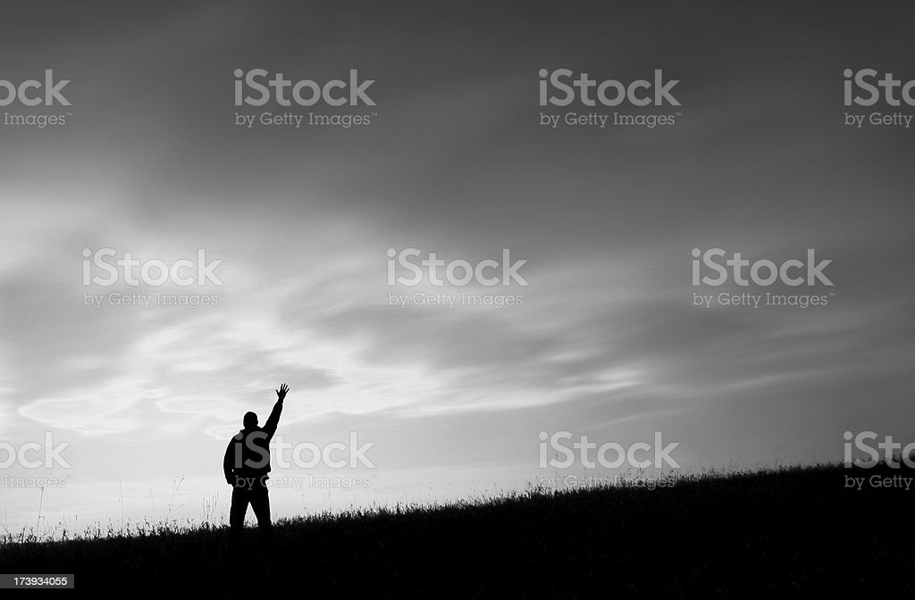 Black and White Image of a Man on a Hill Reaching To Heaven royalty-free stock photo