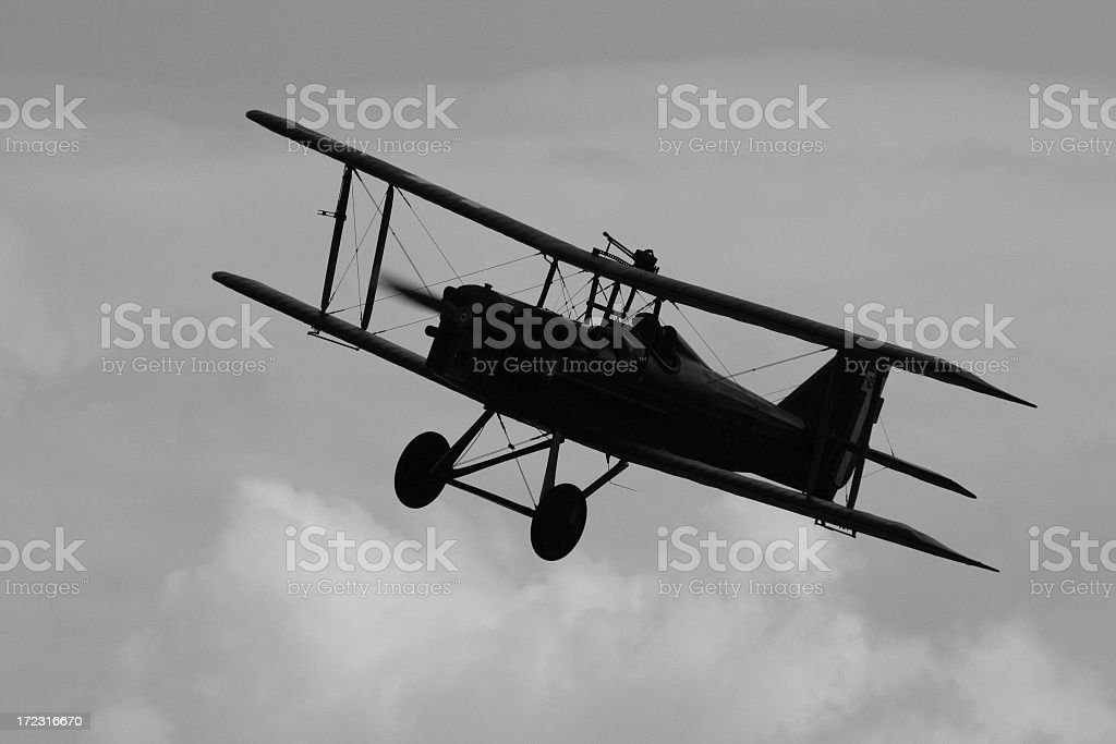 Black and white image of a WWI biplane flying in the air stock photo