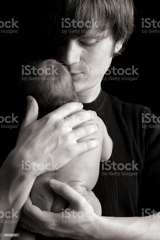Black and White Image of Father Sheltering His Newborn royalty-free stock photo