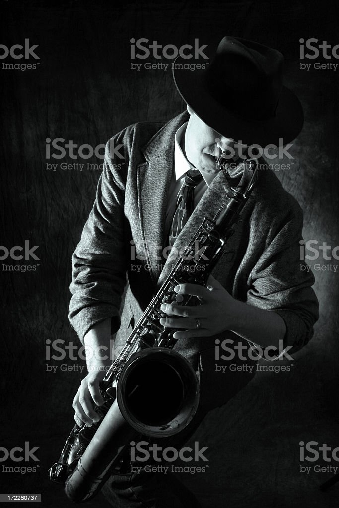 Black and white image of man in a hat playing the Saxophone royalty-free stock photo