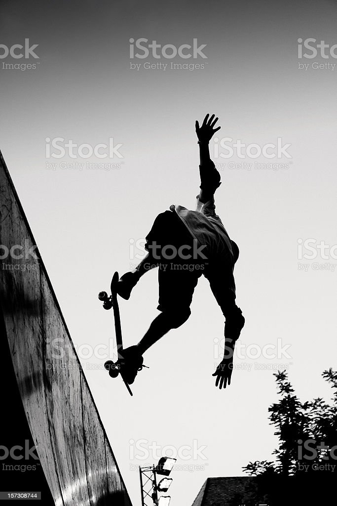 Black and white image of man performing a skateboard jump stock photo