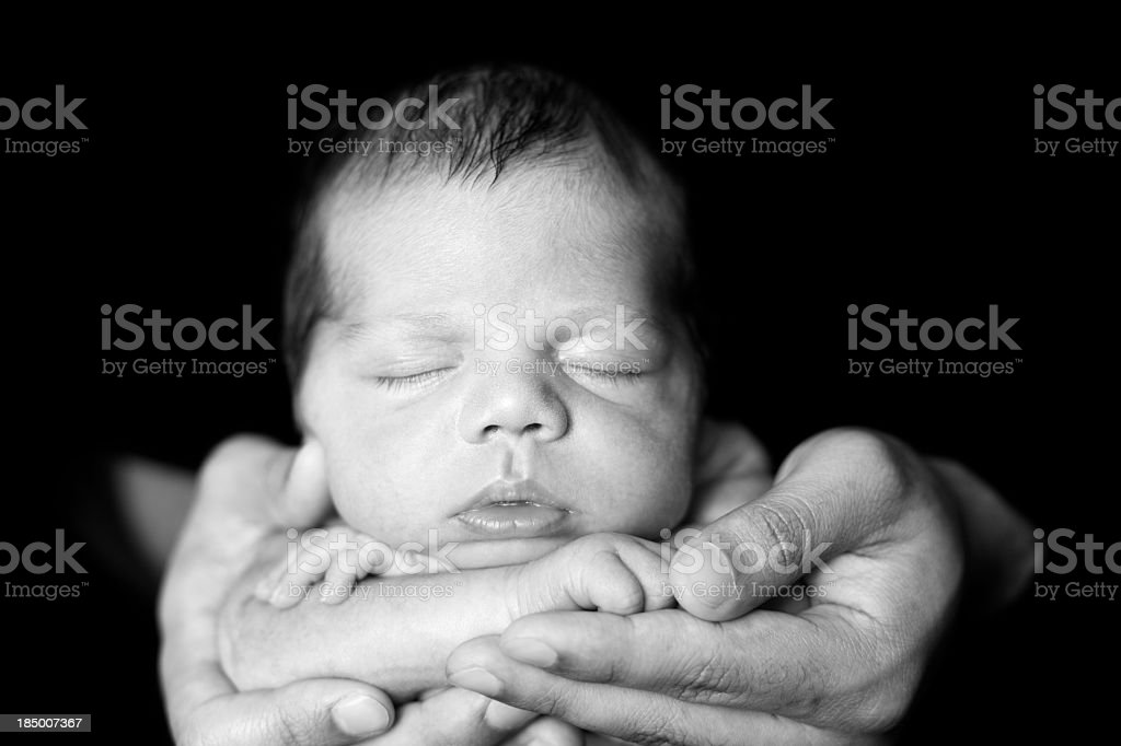 Black and White Image of Newborn Sleeping in Father's Hands royalty-free stock photo