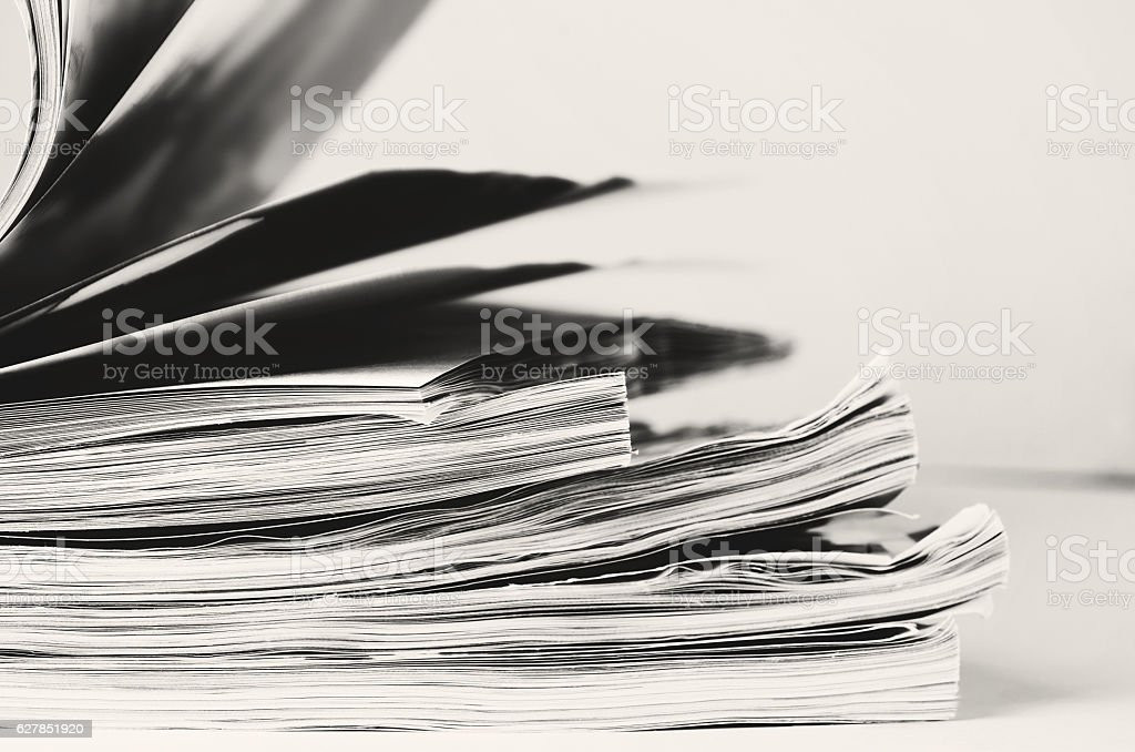 black and white image stack of magazines to turn pages stock photo