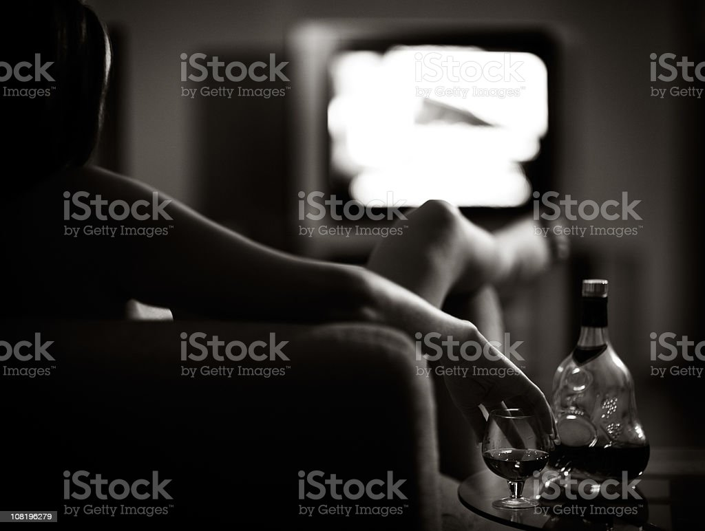 Black and White Low-Key Image of Woman Drinking Cognac royalty-free stock photo