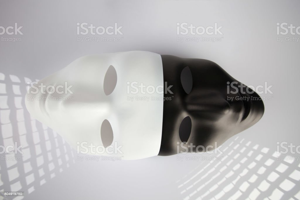 Black and white masks joined on white reflective background, top view. Anonymity concept. stock photo