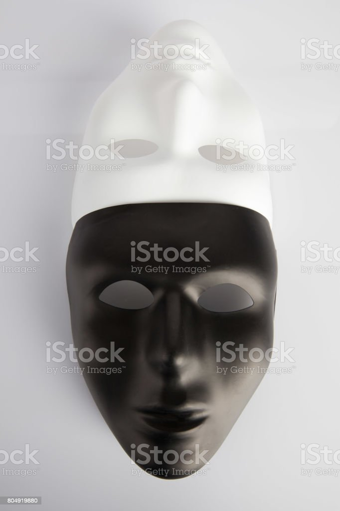 Black and white masks joined on white reflective background. Vertical image, top view. Anonymity concept. stock photo