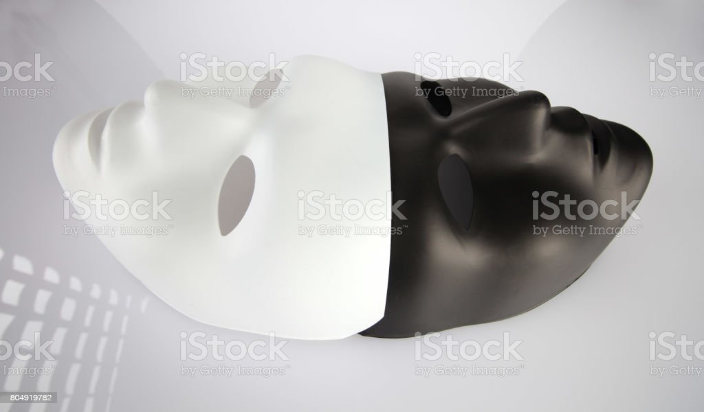 Black and white masks joined on white reflective background, wide angle view. Theater and anonymity concept. stock photo