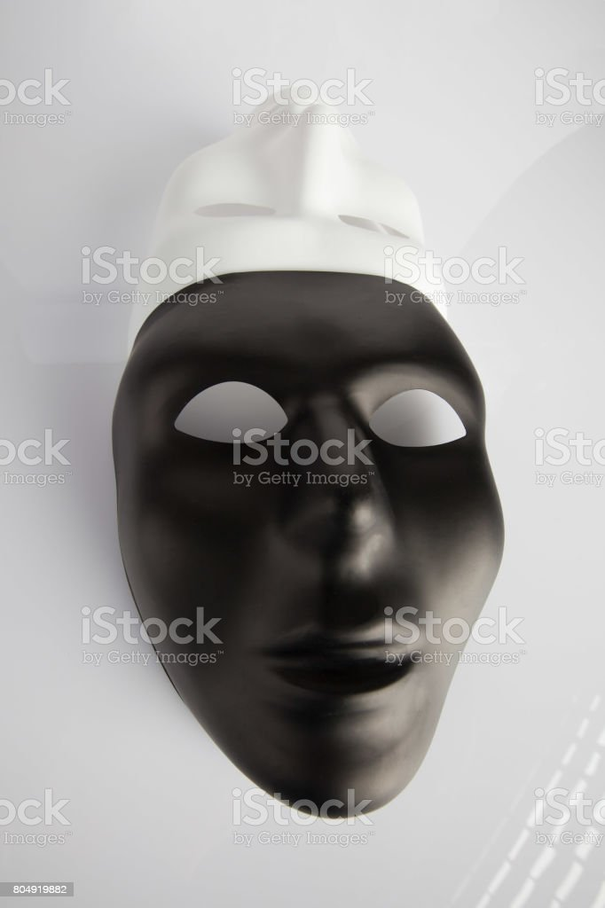 Black and white masks joined on white reflective background. Wide angle, vertical image, top view. stock photo