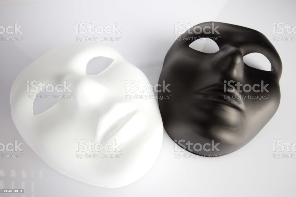 Black and white masks on white surface  - looking upwards stock photo