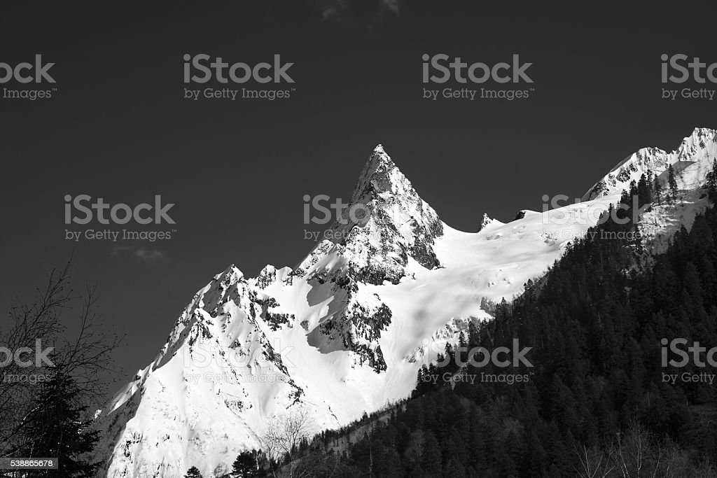 Black and white mountain peak in snow stock photo
