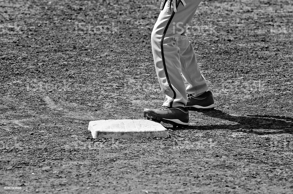 Black and white of close up of baseball base and players stock photo