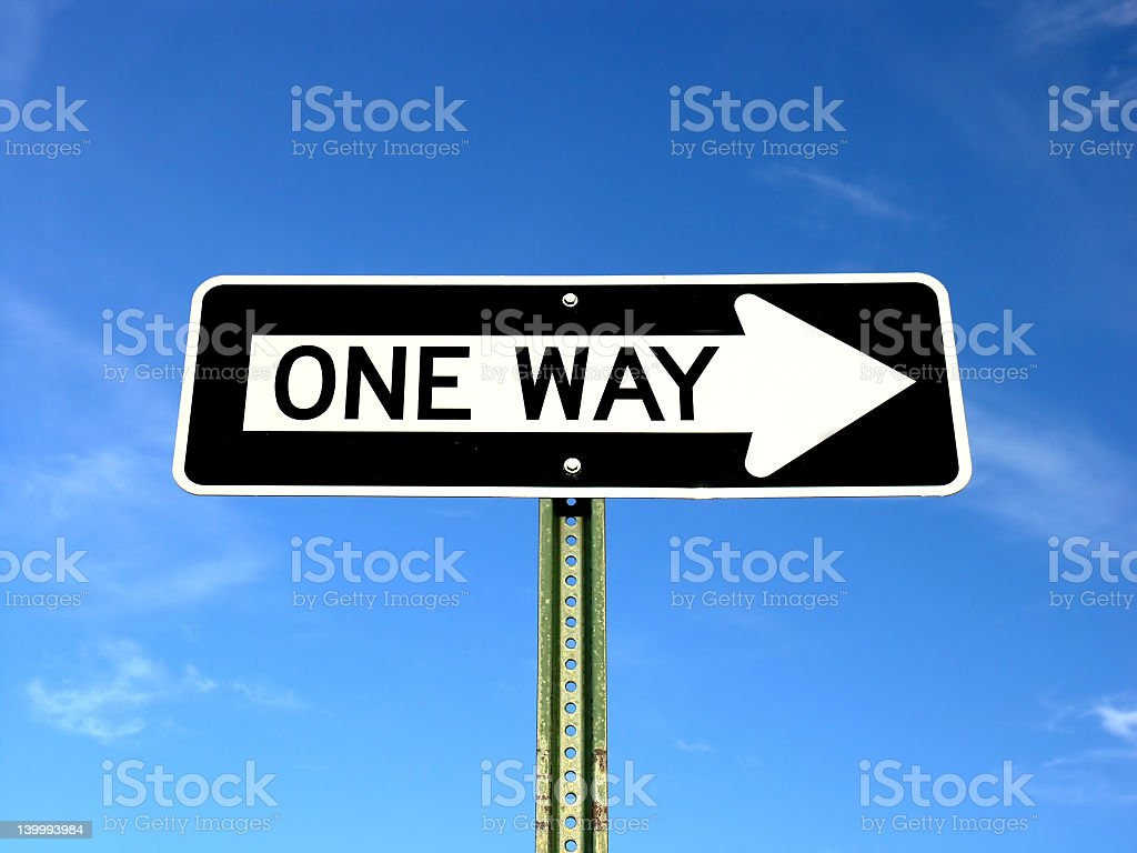 Black and white one way sign with blue sky stock photo