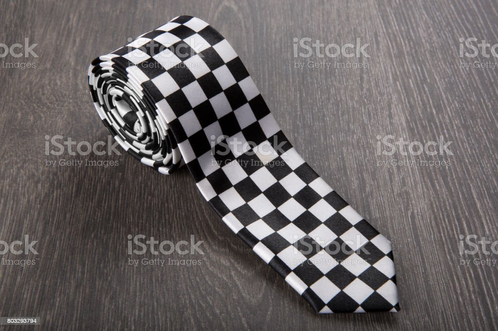 Black and white patterned tie on wooden background stock photo