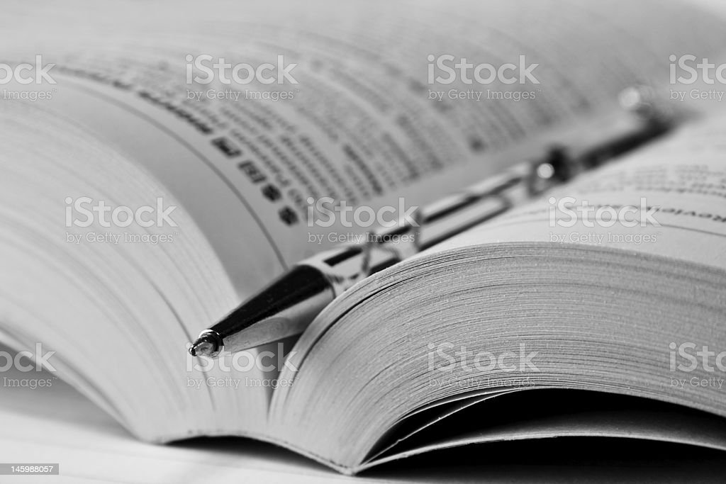 A black and white pen lying in the spine of an open book royalty-free stock photo
