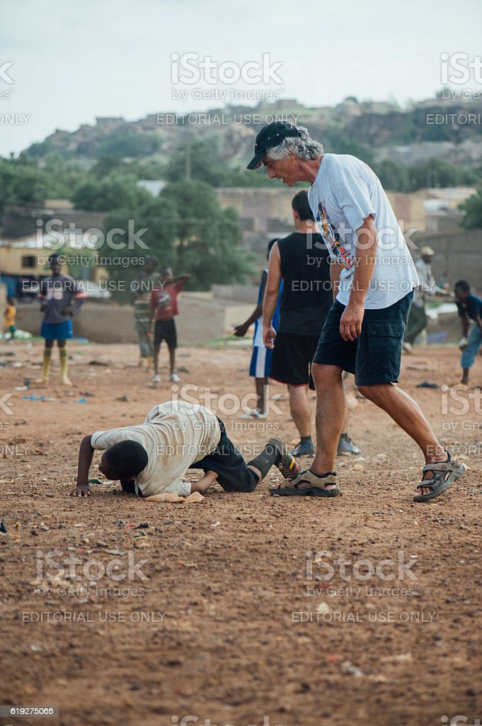 Black and white people playing soccer in a african village stock photo