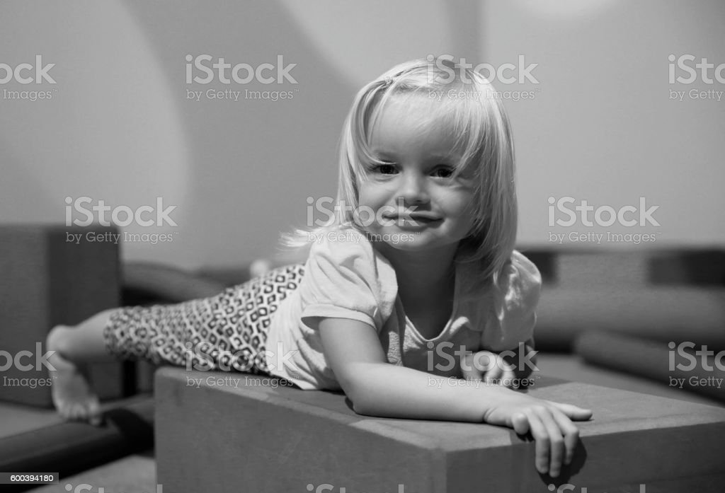 Black and white photo. Cute Little girl in playing room stock photo