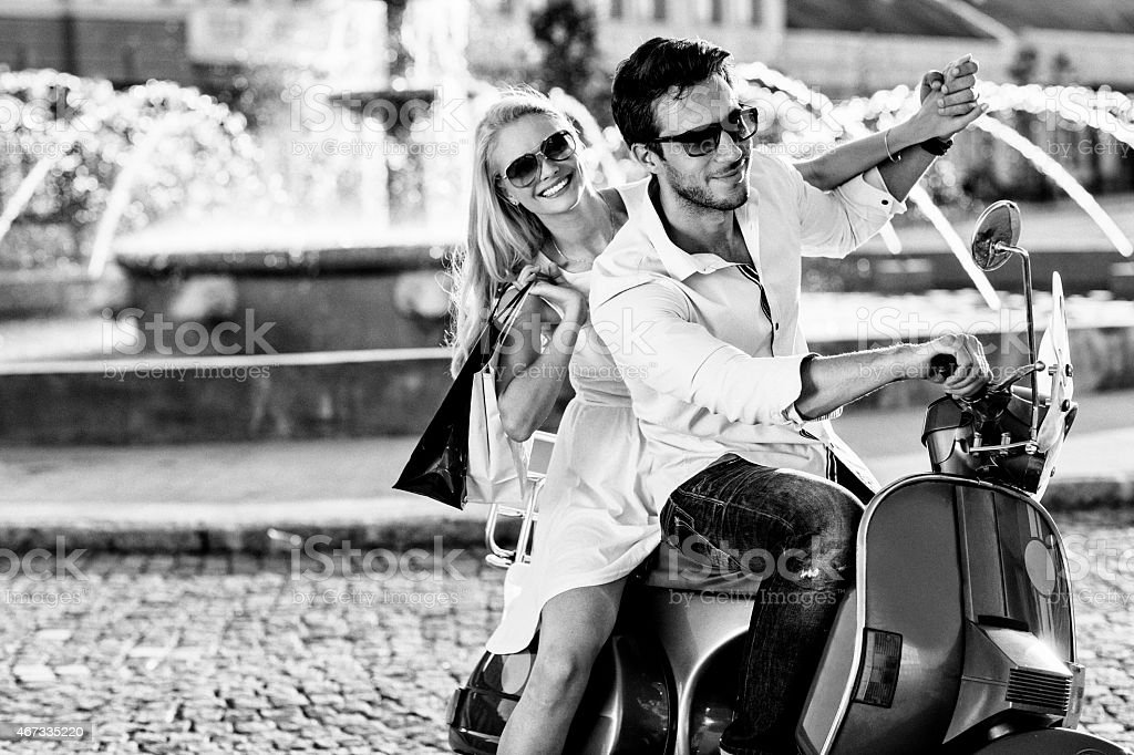 Black and white photo of a beatiful couple driving scooter stock photo