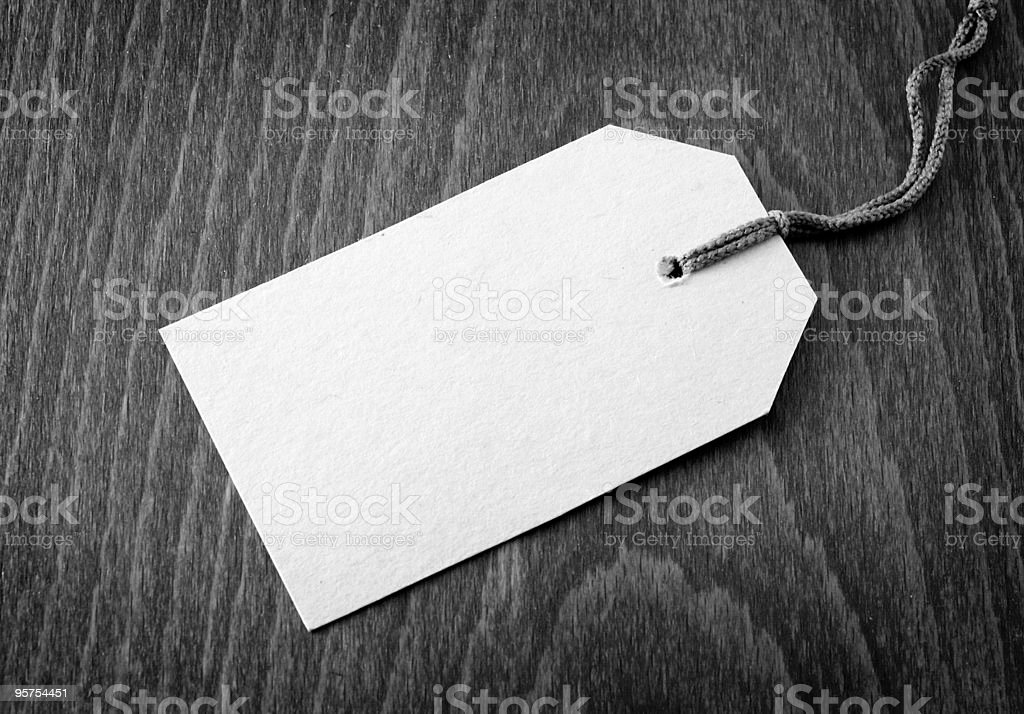 Black and white photo of a blank, stringed tag, set on wood stock photo