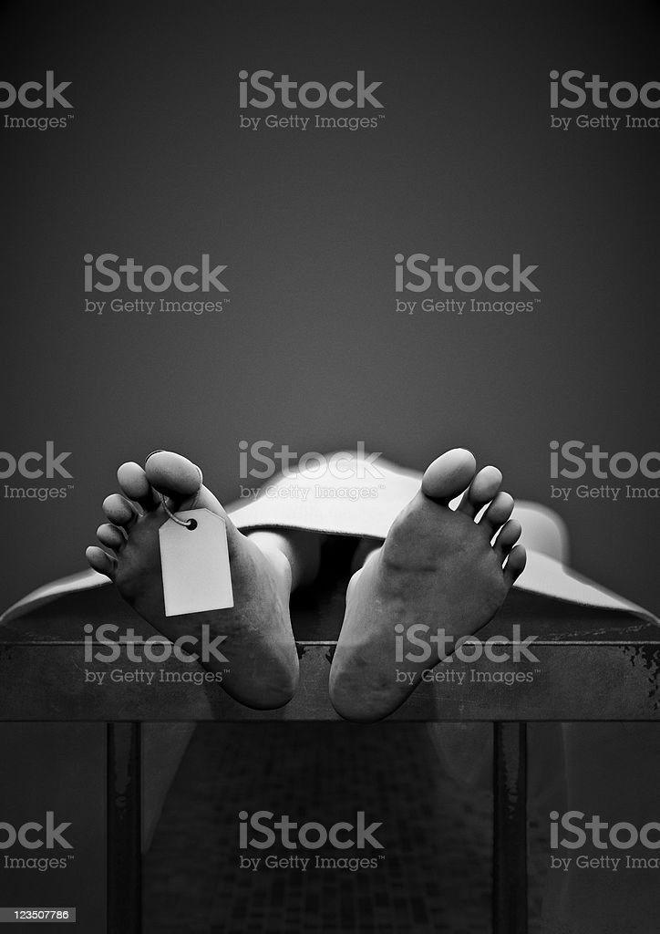 Black and white photo of a dead man's feet with toe tag stock photo