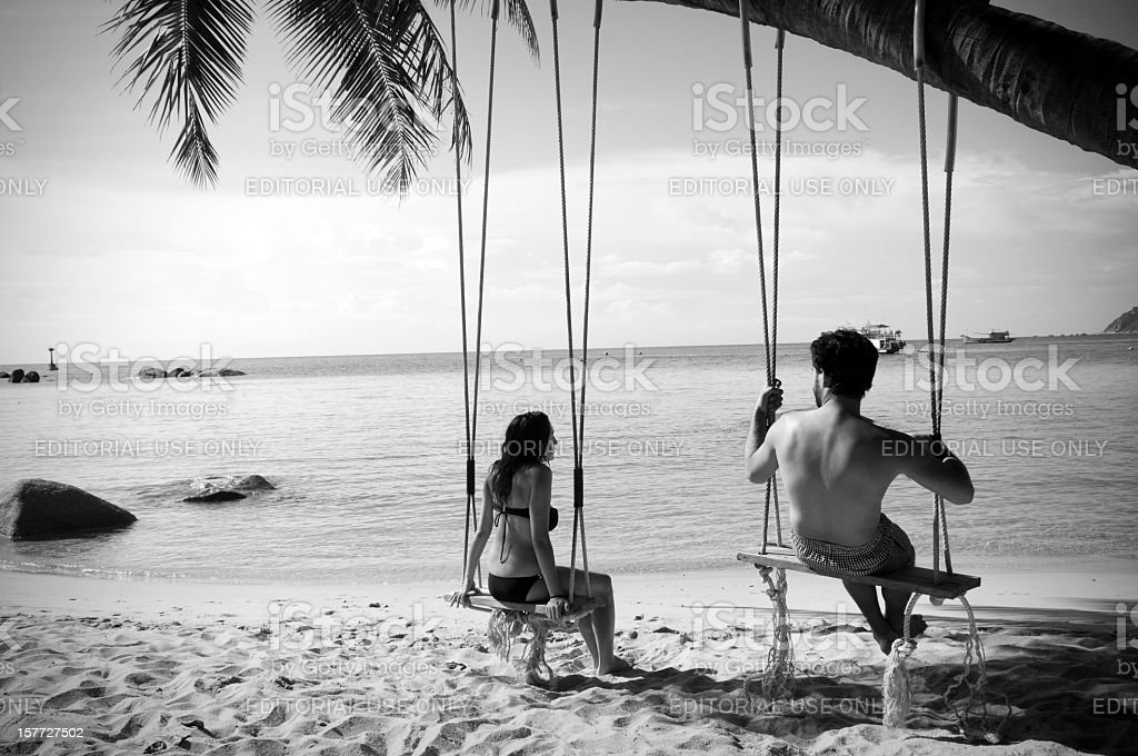 Couple on rope swing at beach in Thailand royalty-free stock photo