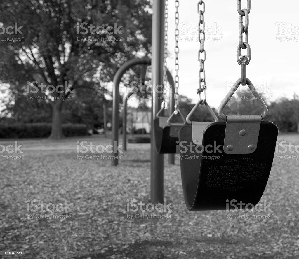 A black and white photo of a swing set stock photo