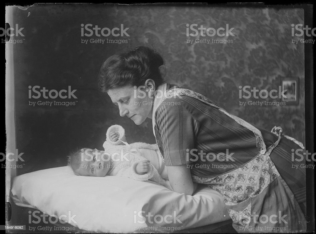 Black and white photo of caring mother leaning over her baby stock photo