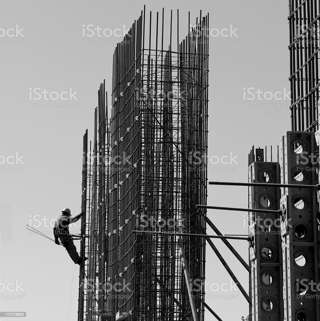 Black and white photo of construction worker on supports royalty-free stock photo