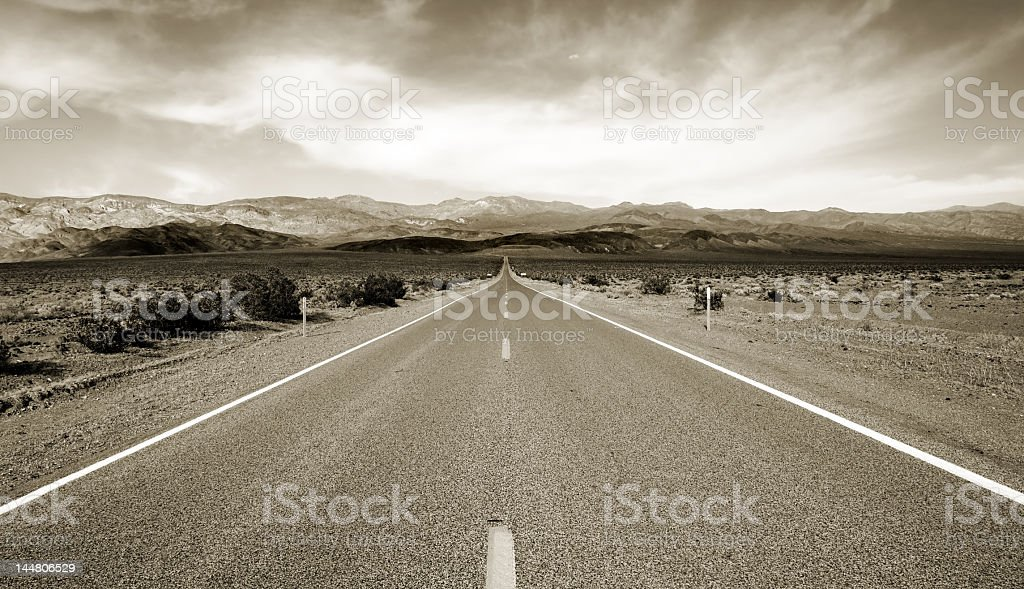 Black and white photo of highway through desert stock photo
