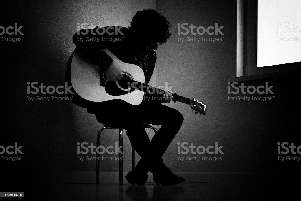 Black and white photo of man playing guitar stock photo