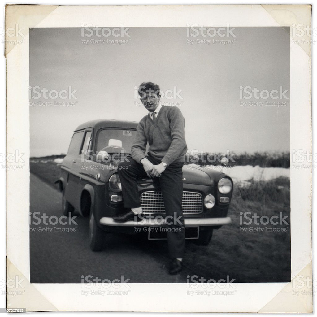 Black and white photo of man sitting on vintage car bonnet royalty-free stock photo