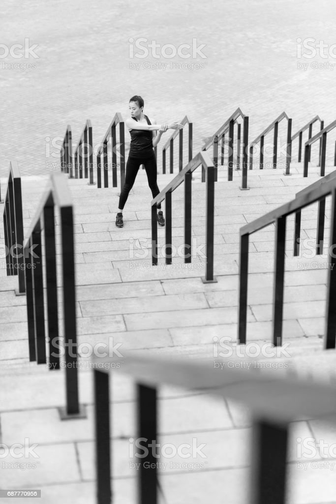 Black and white photo of sporty young woman exercising on stadium stairs stock photo