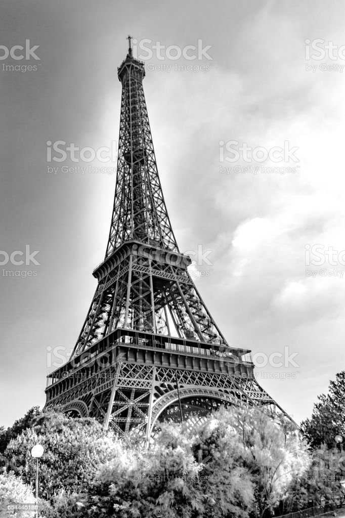 Black and white photo of the Eiffel tower under a cloudy sky. Symbol of Paris, France. stock photo